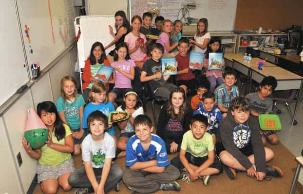Debbie Pavlove's Breslau PS class hold up Food For Thought, the published book on nutrition they created, from cover to cover, just in time for the end of their fourth-grade school year. [elena maystruk / the observer]