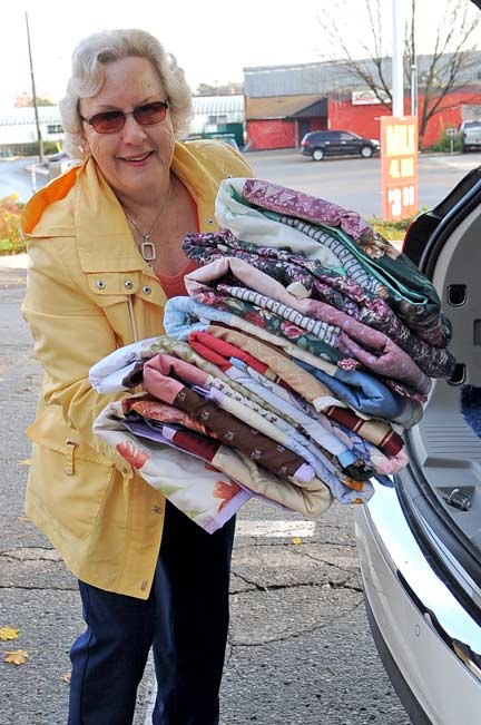 Loraine Berge turns over 283 quilts she made to Pastor Hans Borch  of Elmira's St. James Lutheran Church, which is taking part in a drive to help Syrian refugees.[Will Sloan / The Observer]