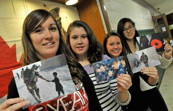 Staff member Erin Westra and EDSS students Melanie McArdle, Alex Hahn and Maddie Wang hold up some war-themed images from the Remembrance Day display still in the school hall this week. [Elena Maystruk / The Observer]